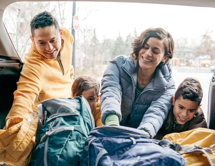 Family packing bags in car