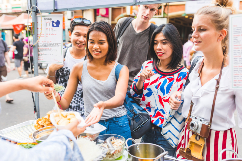 group of people waiting around a market stall for food, smiling