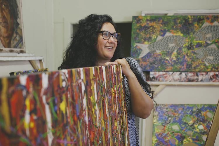 aboriginal artist standing with her work