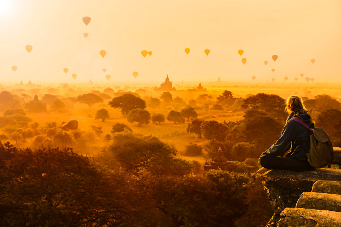 girl on temple overlooking balloons and temples at sunrise myanmar