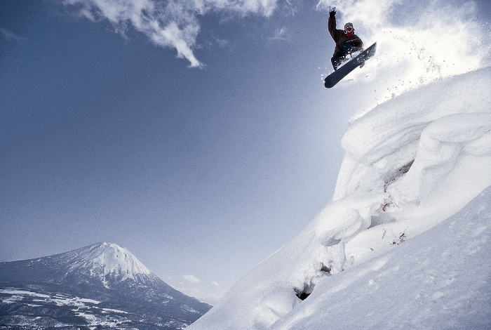 snow boarder jumping off mountain with mount fuji behind