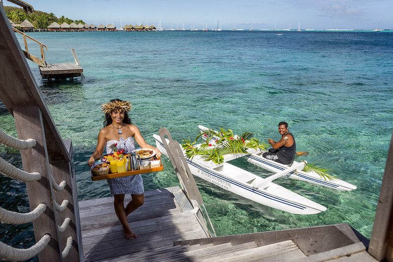 Photo of two locals bringing room service to the overwater bungalow