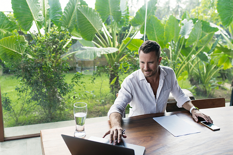 Man works on a laptop with a garden backdrop in Bali