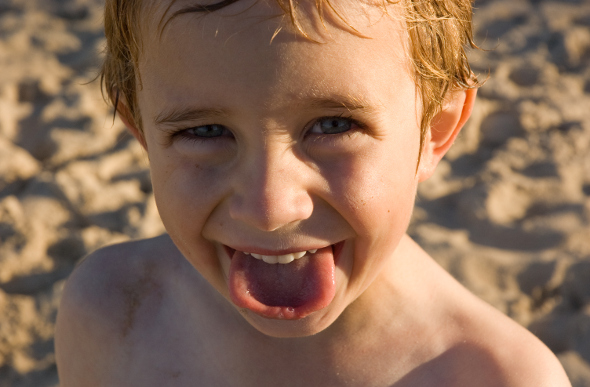 A closeup of a cheeky boy on the beach at Port Macquarie, New South Wales.