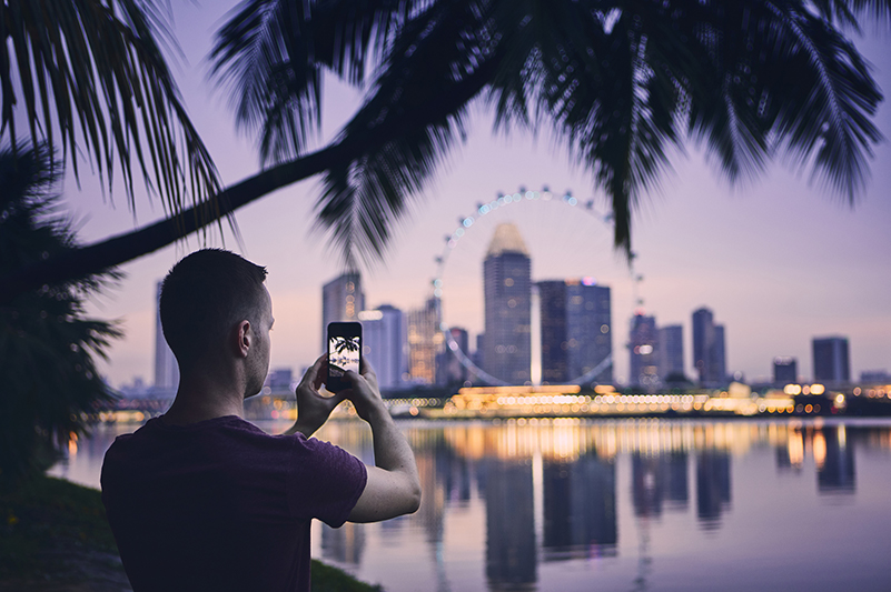 Man taking photo of Singapore cityscape with smartphone at night.