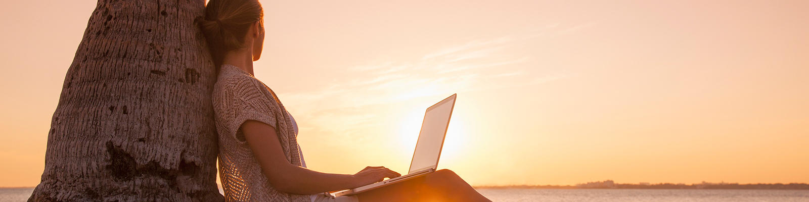 Working on a laptop during a beach sunset