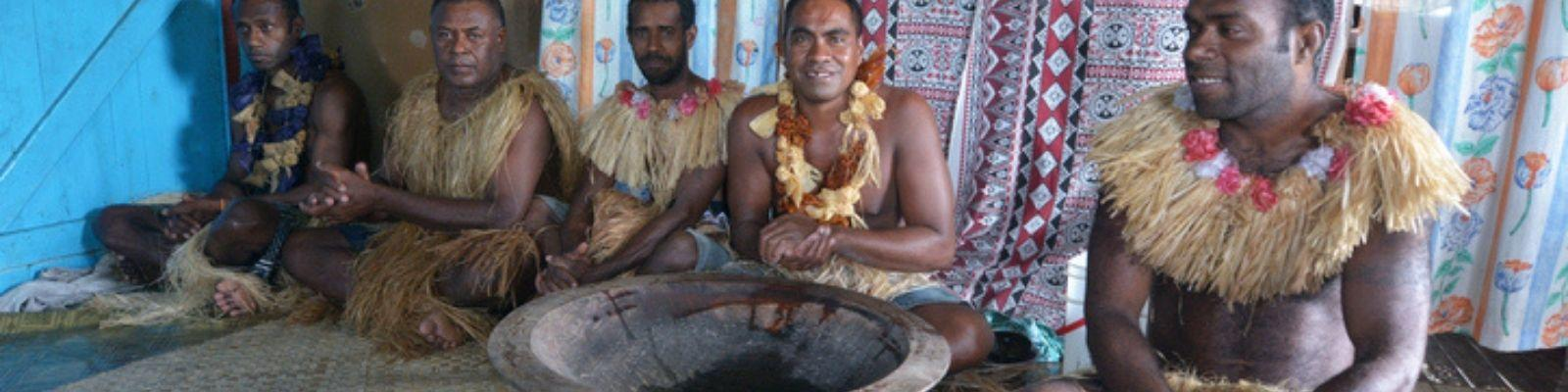 Fijian men sitting on straw mat with bowl of kava in front