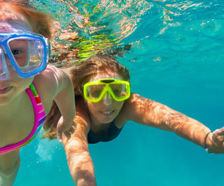 two girls snorkeling underwater and looking at the camera