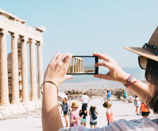 woman holding up a phone to take a photo in Athens